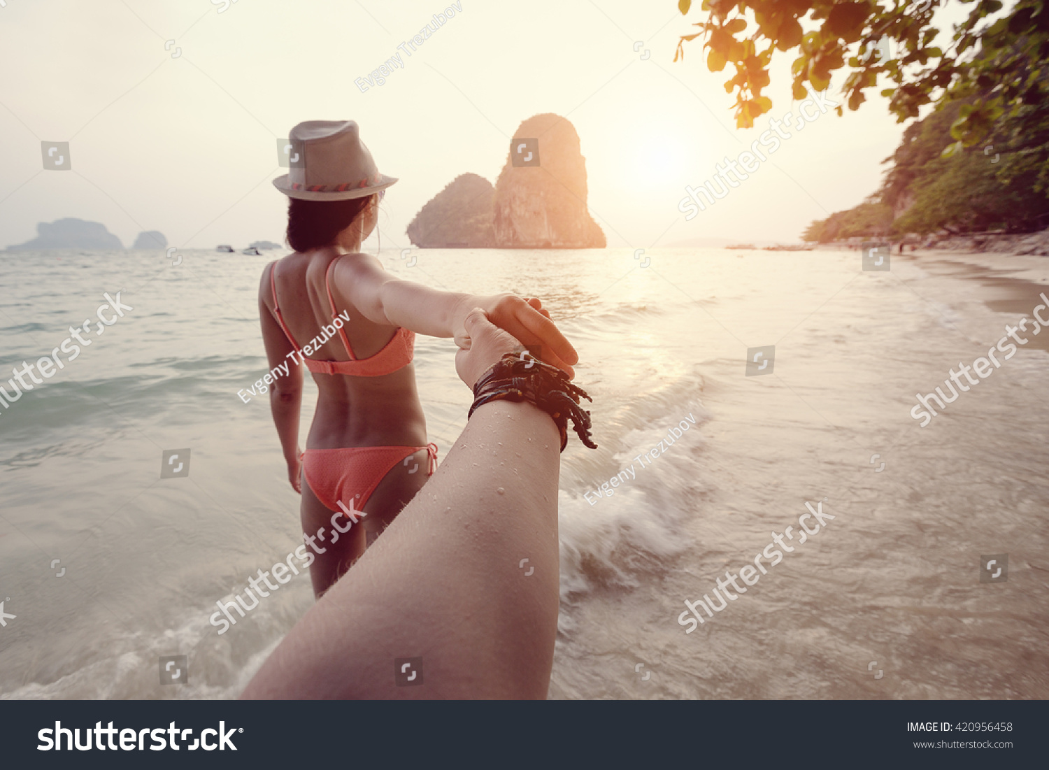 Girl in a bikini holding a hand Man on the beach in Thailand