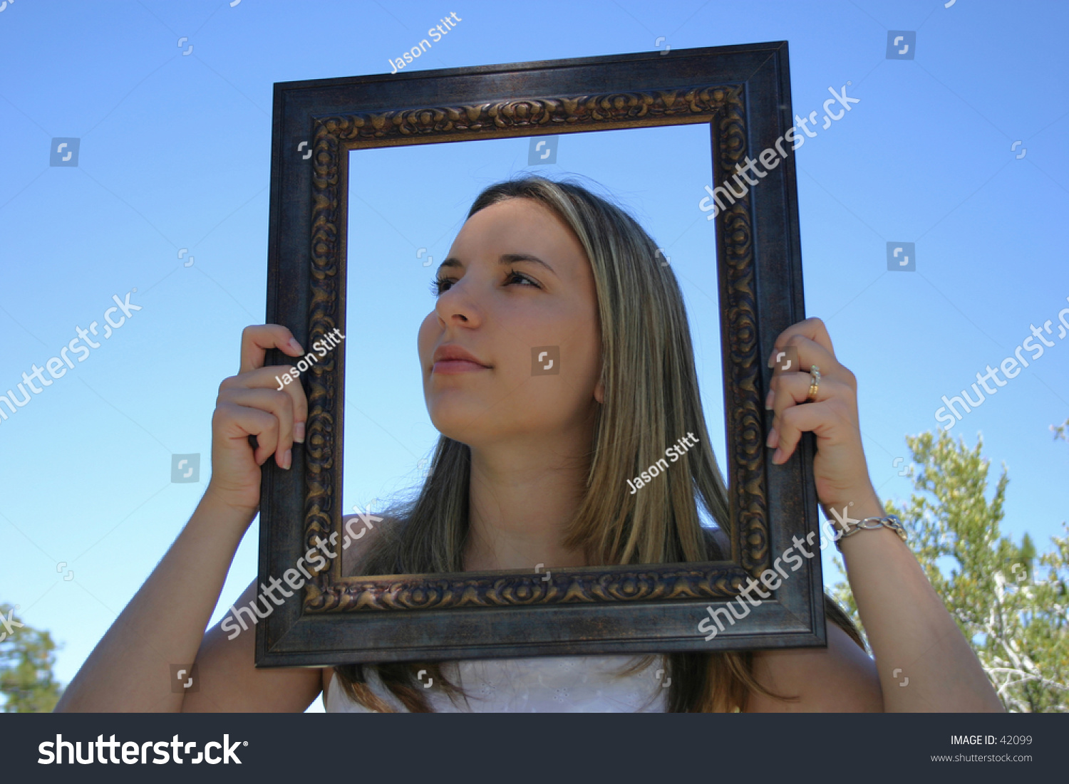 A young woman with her head in a frame