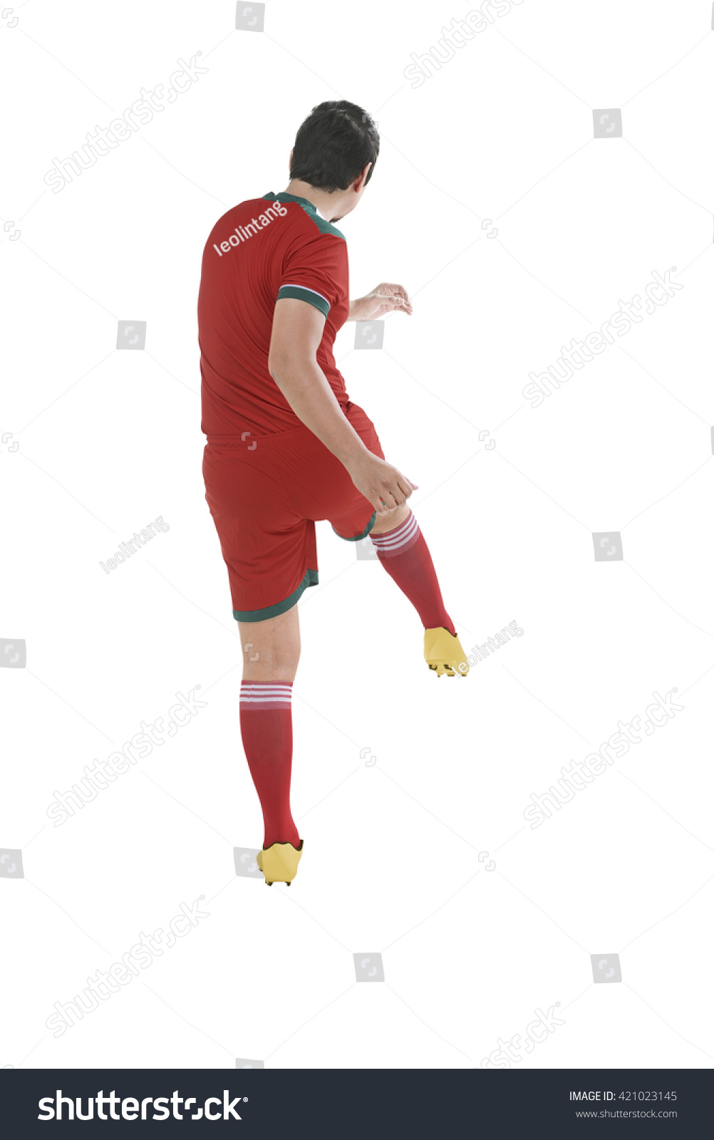 Back view of asian football player kick ball isolated over white background