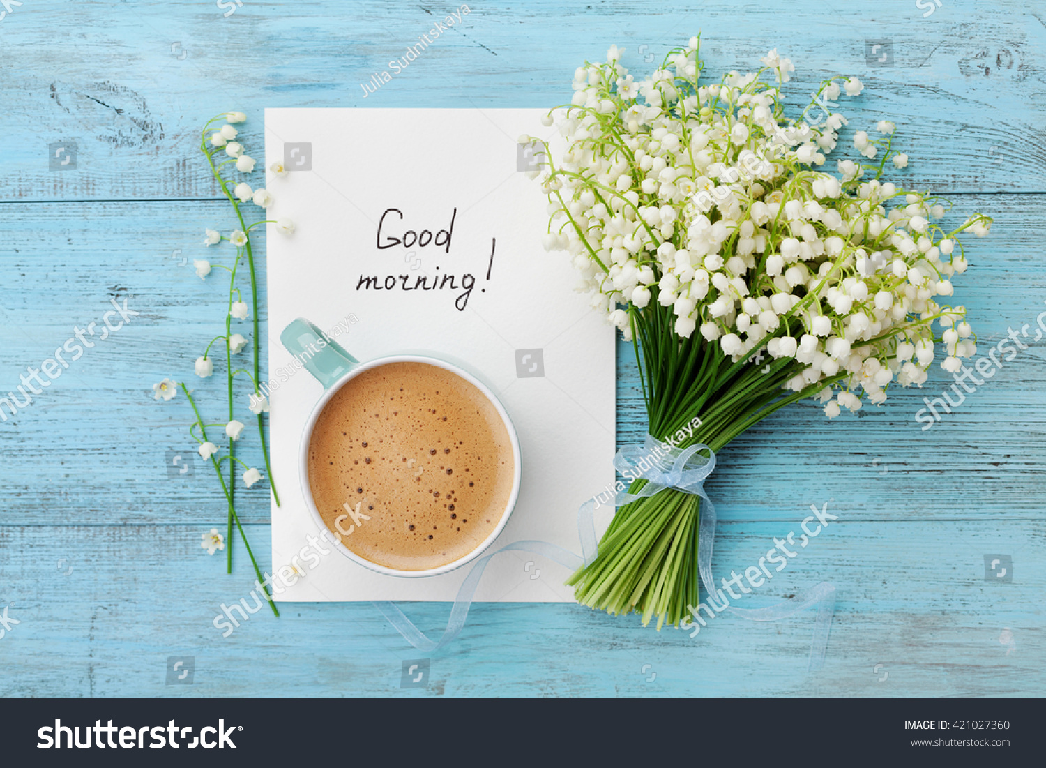 Coffee mug with bouquet of flowers lily of the valley and notes good morning on turquoise rustic table from above, beautiful breakfast, vintage card, top view, flat lay #421027360