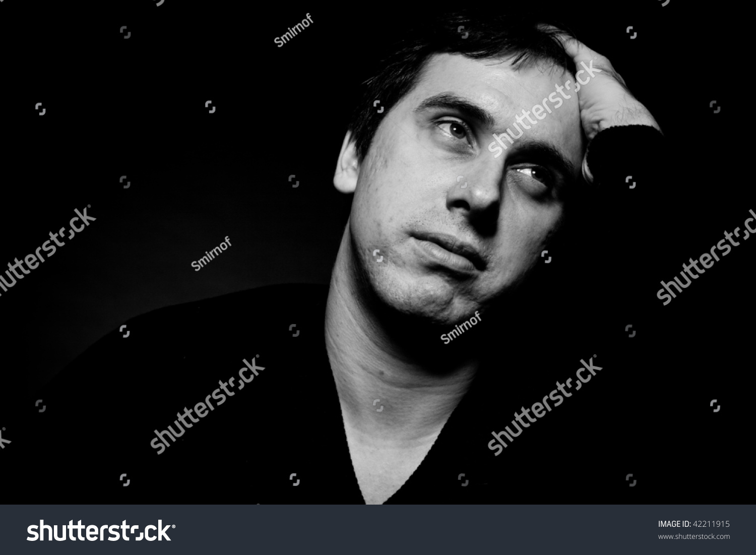 black background young caucasian man staring serious close