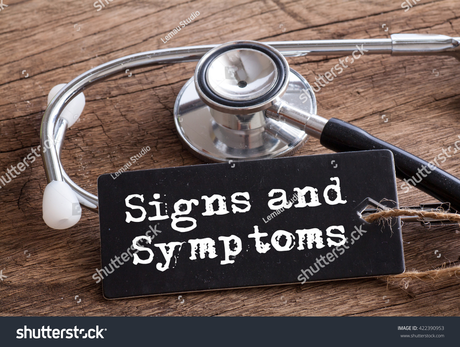 Stethoscope on wood with Signs and Symptoms words as medical concept #422390953