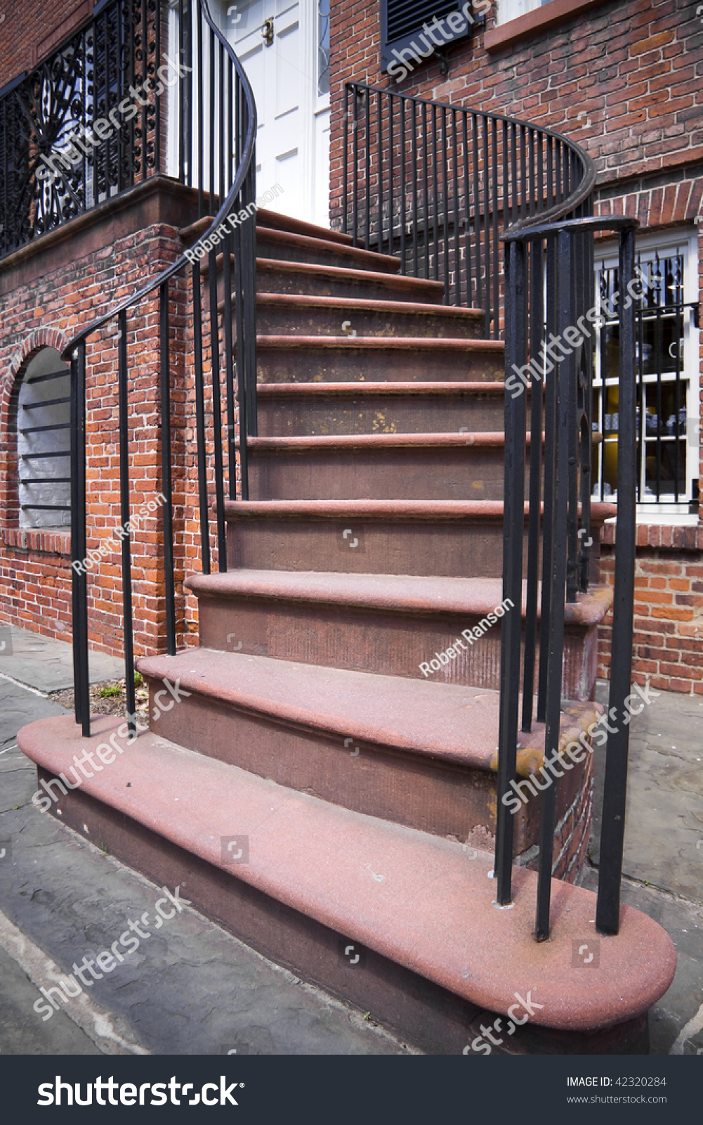 Brick Staircase With Black Metal Hand Rails Leading To The