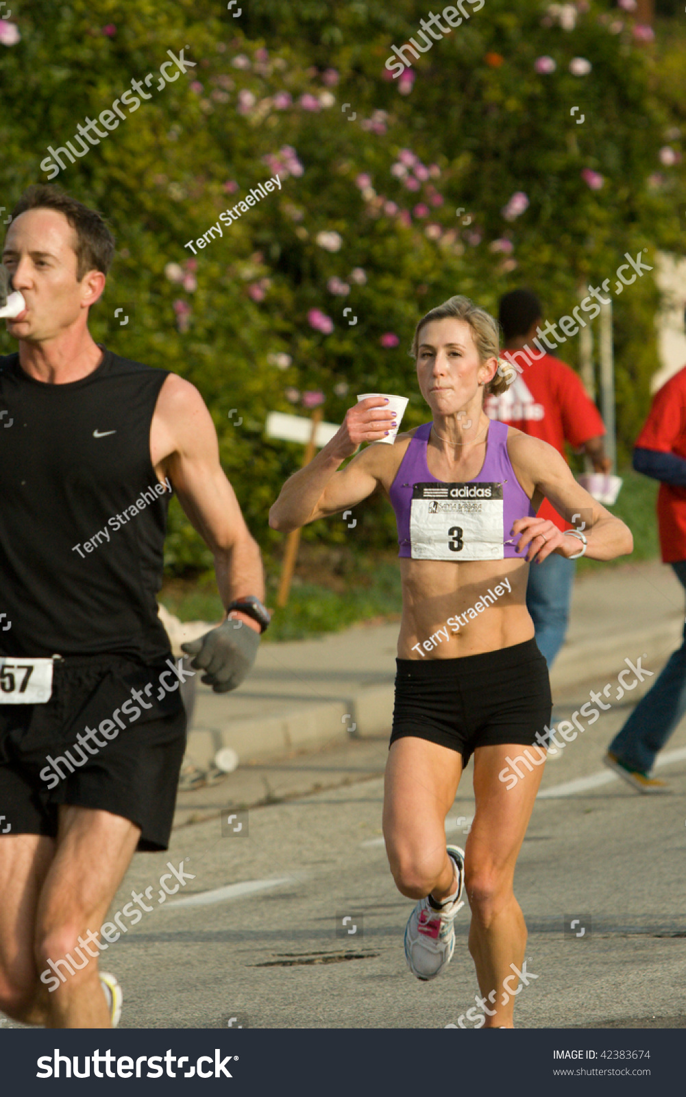 SANTA BARBARA, CA - DEC. 06: Andrea McLarty (1st female, 11th) is refreshed  at a water stop at the Select Staffing Santa Barbara International Marathon  on ...