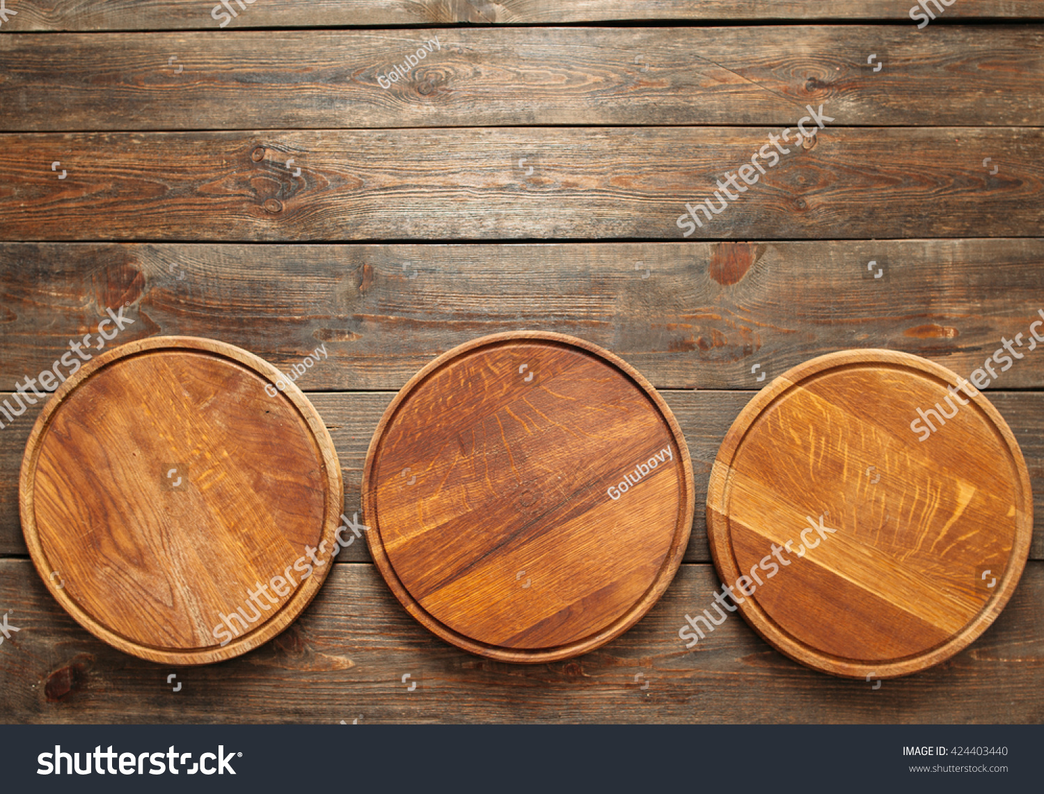 Three empty wooden pizza plates lie on the wooden table at the bottom of the picture & Royalty-free Three empty wooden pizza plates lie onu2026 #424403440 ...