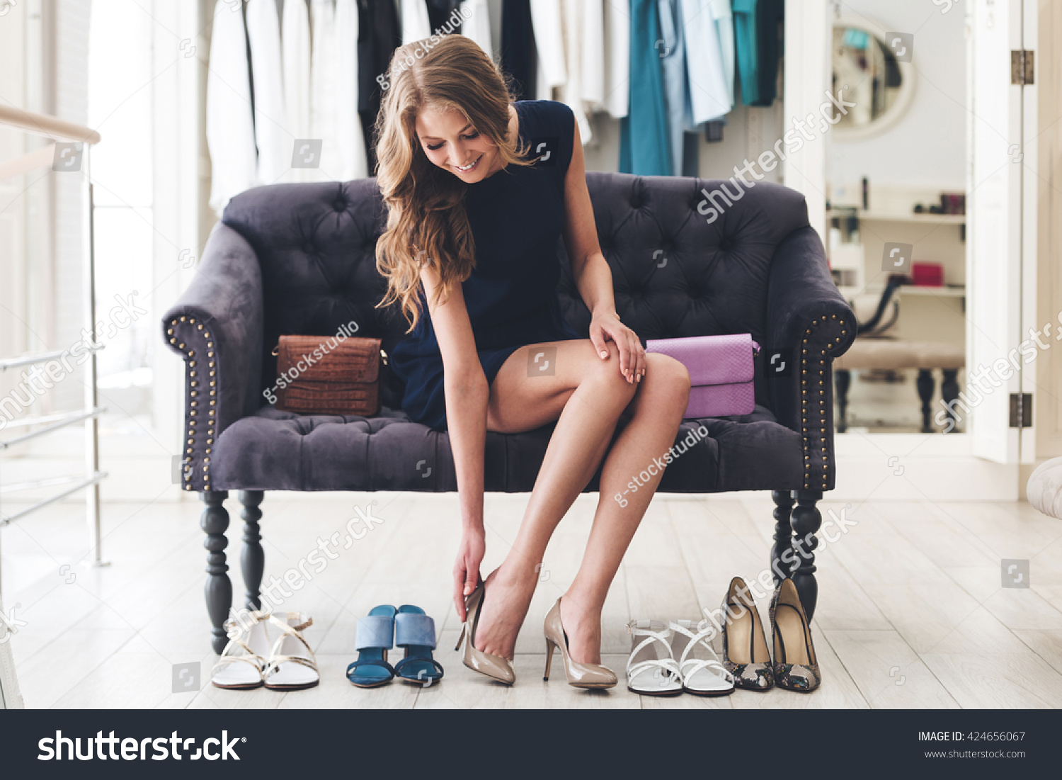 That is perfect pair! Beautiful young woman trying on high heel shoes while sitting on sofa at the shoe store #424656067
