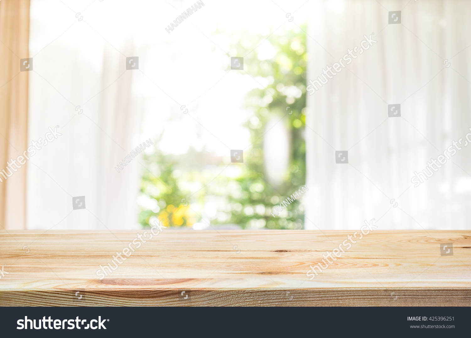 Empty of wood table top on blur of curtain window and abstract green from garden with sunlight .For montage product display or design key visual layout