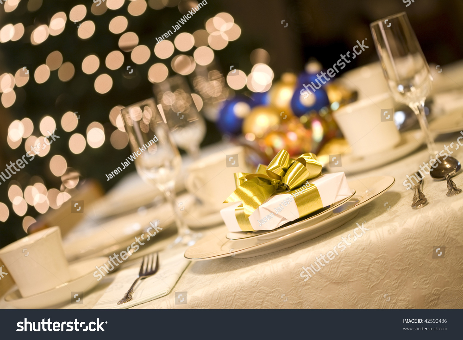 Dinner table background - Gold Present On Dining Table With Christmas Tree Lights In Background