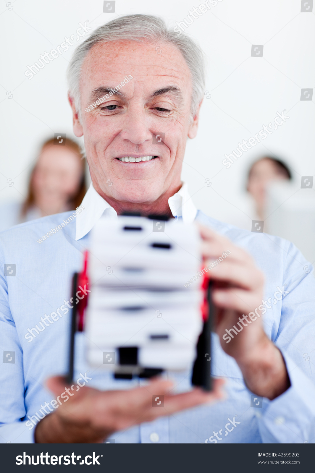 Senior businessman holding business card holder stock photo royalty senior businessman holding a business card holder in an office reheart Image collections