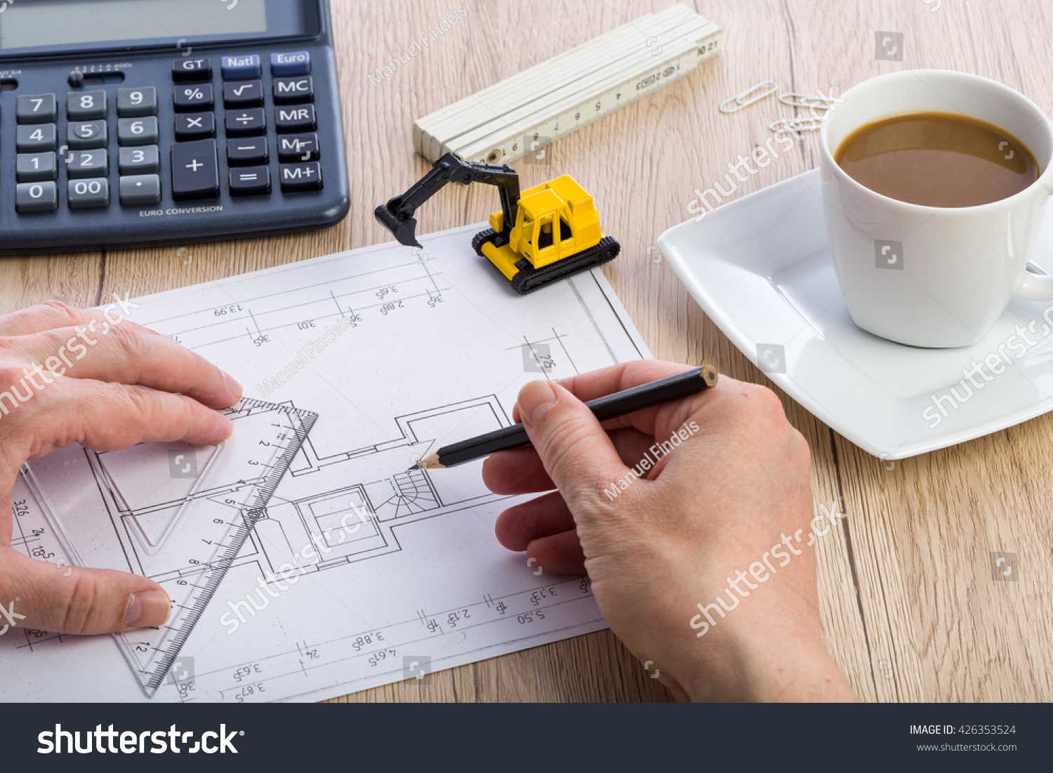 Closeup architect hands working on blueprint stock photo edit now close up of architect hands working on a blueprint calculator cup of coffee malvernweather Images