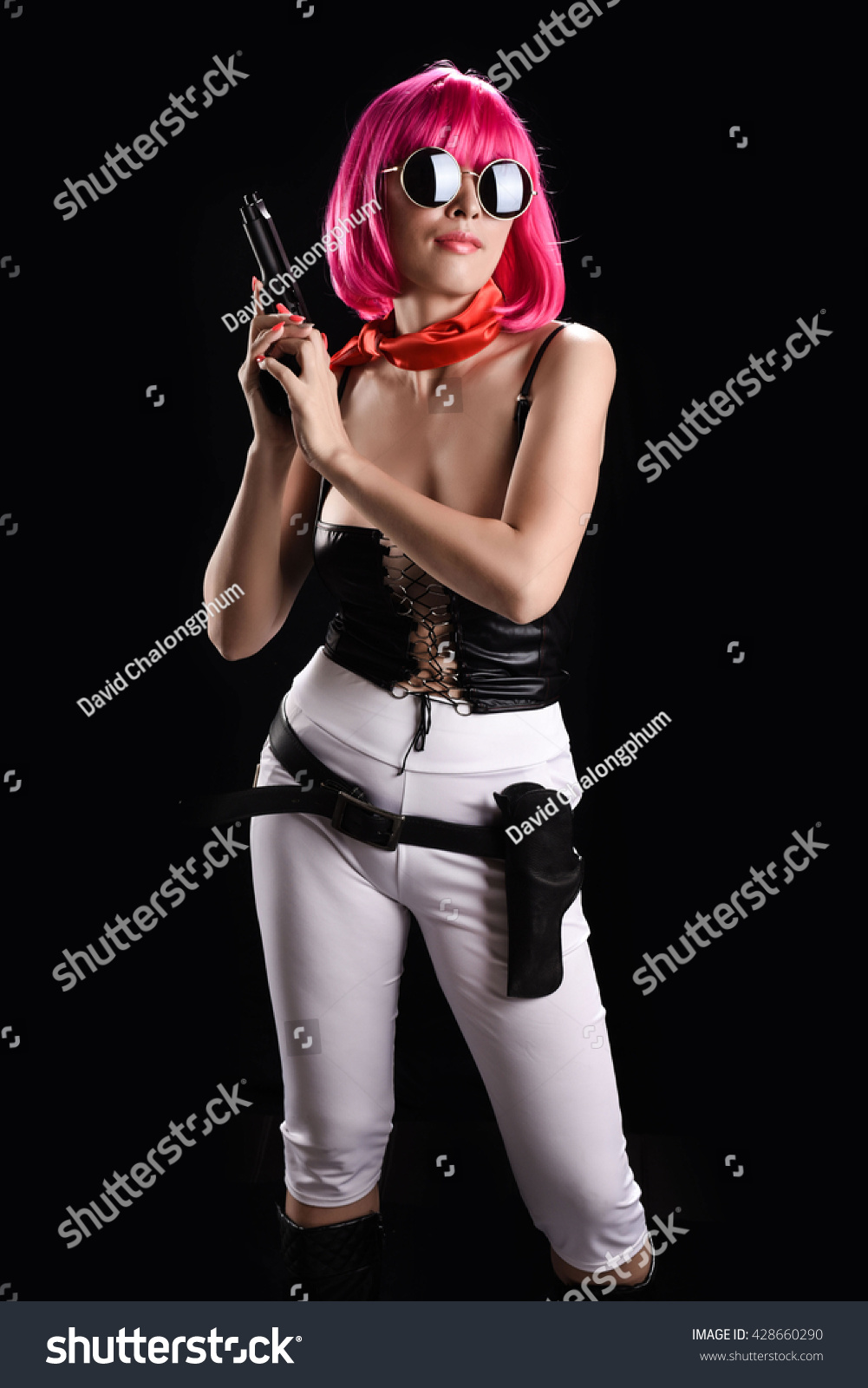 Studio shot Sexy beauty killer women wearing action suit holding the gun  isolate in black background