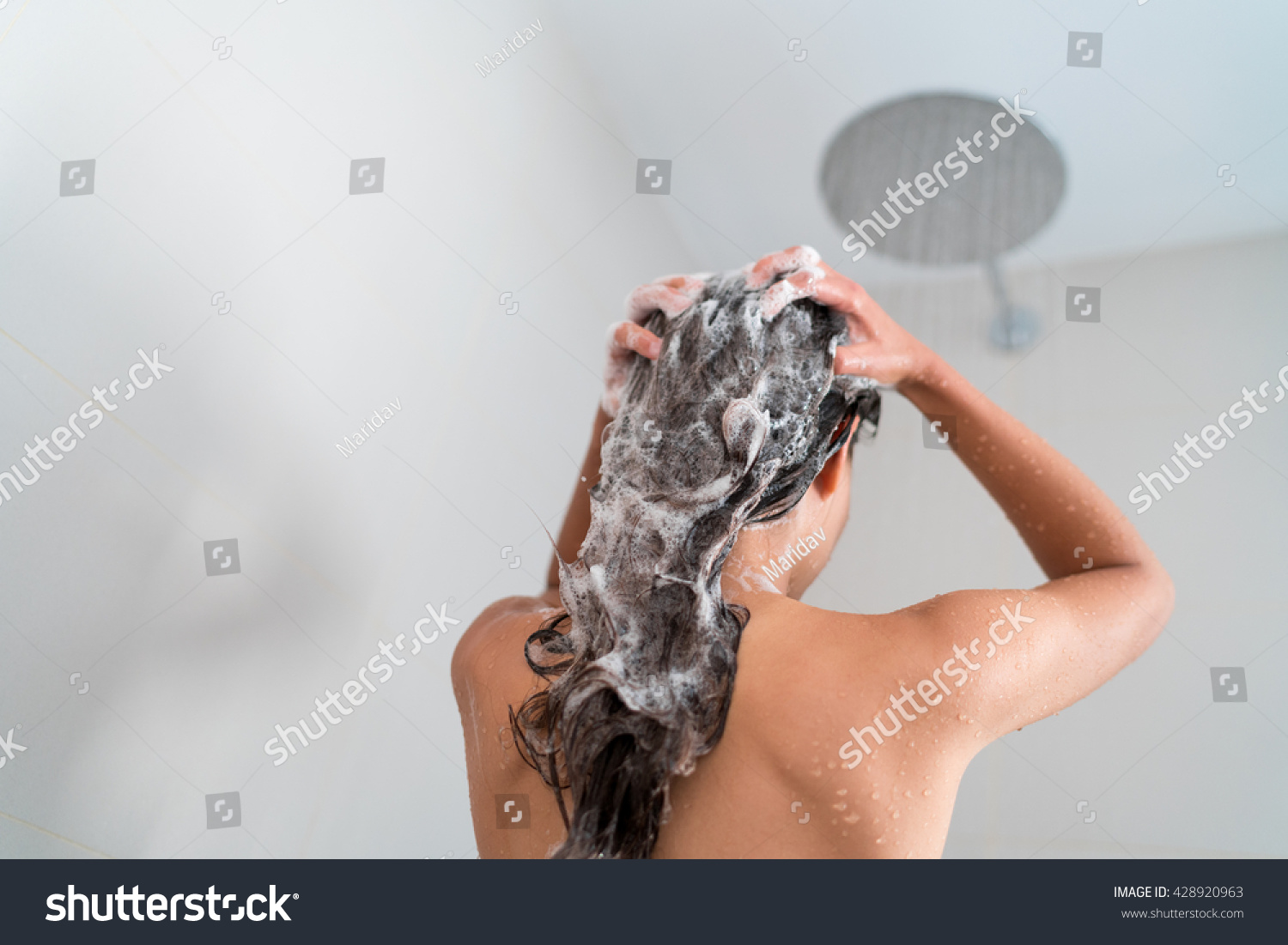 Shower woman washing hair showering in bathroom at home Unrecognizable person from behind rinsing shampoo and conditioner from her long hair in warm bath with modern ceiling rain water nozzle head