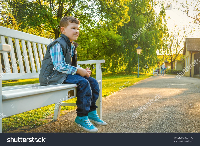 Child Sitting On Park Bench Stock Photo 428994178