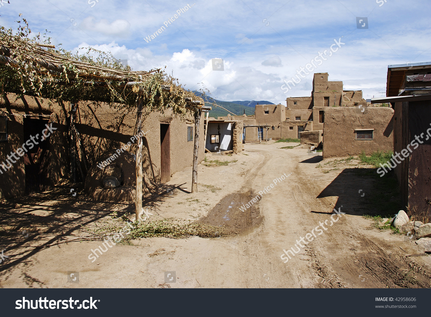 A back street leading through the adobe homes of taos for Adobe construction pueblo co