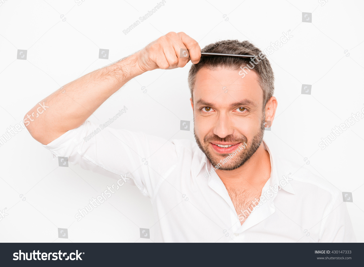 Attractive man combing his hair on white background