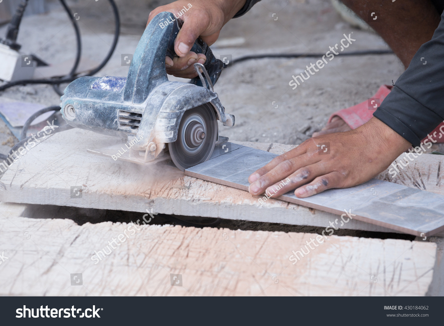 Worker cutting tile using angle grinder stock photo 430184062 worker cutting a tile using an angle grinder at construction site dailygadgetfo Choice Image
