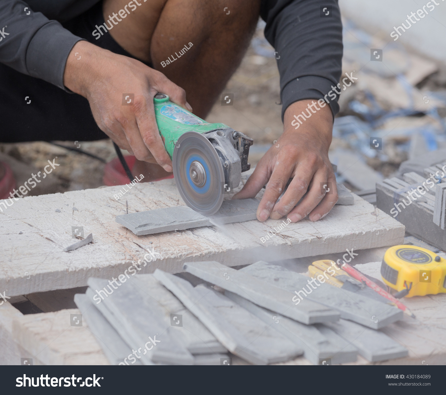 Worker cutting sand stone tile using stock photo 430184089 worker cutting a sand stone tile using an angle grinder at construction site dailygadgetfo Image collections