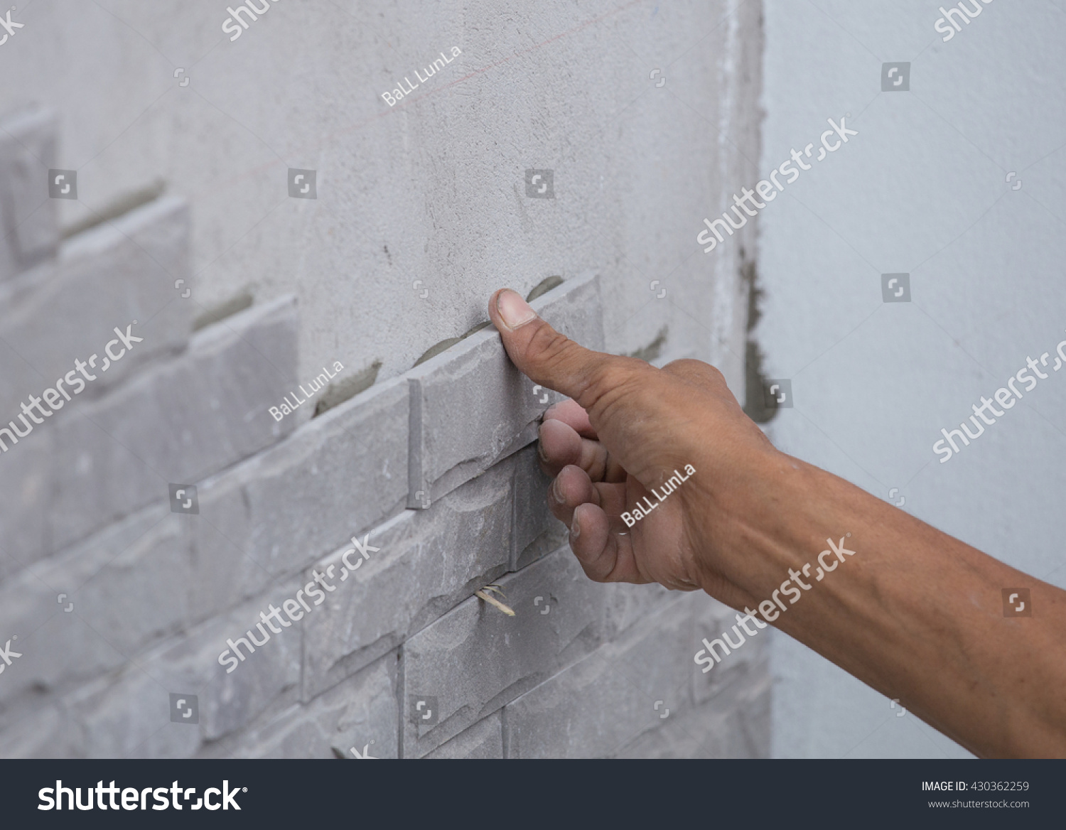 worker install stone wall tile with cement for house decoration #430362259