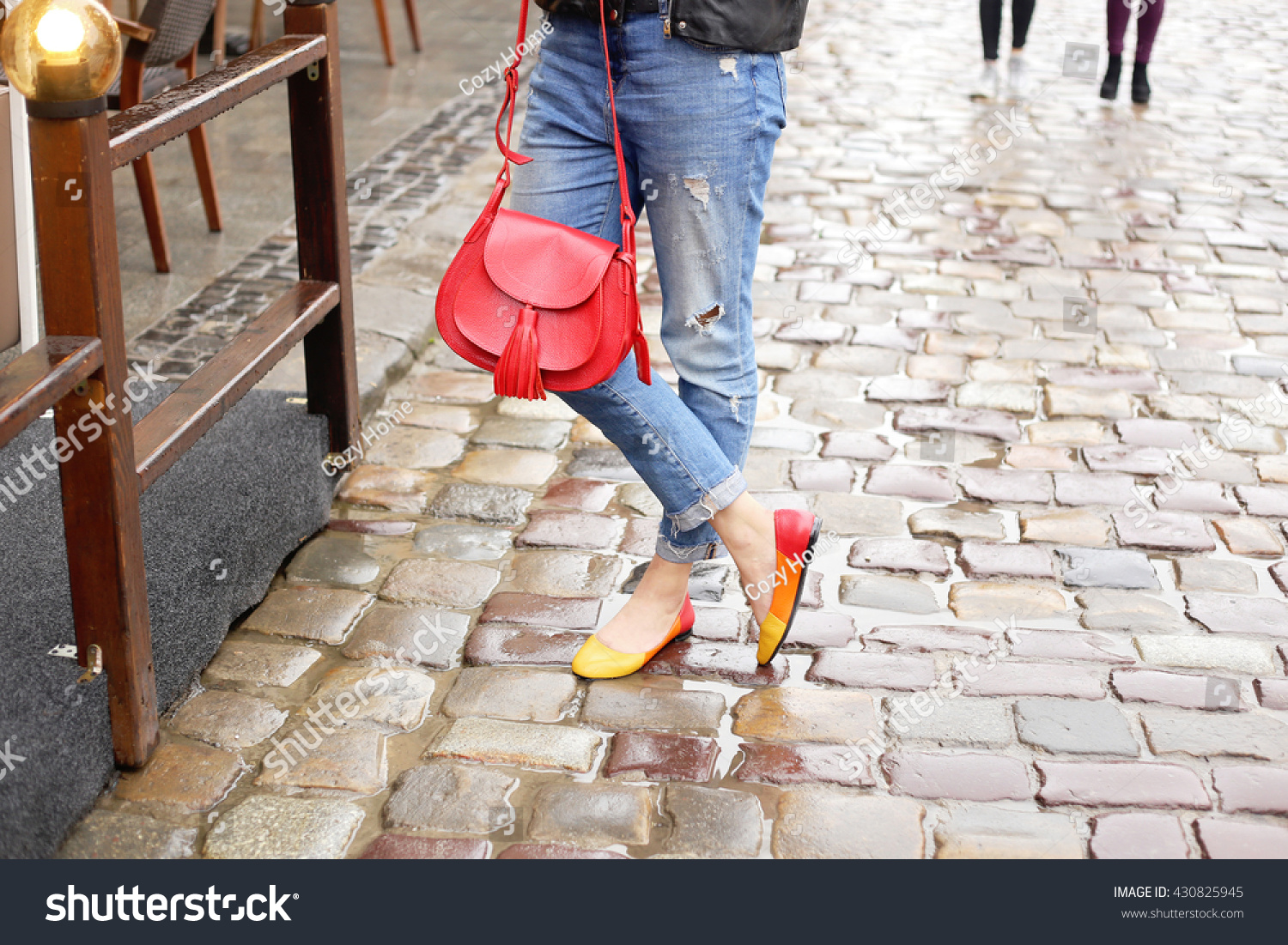 Woman in stylish blue ripped jeans walking down the rainy wet city street with bright red leather handbag and colored ballet flats Street fashion look Legs of a young girl on the wet pavement