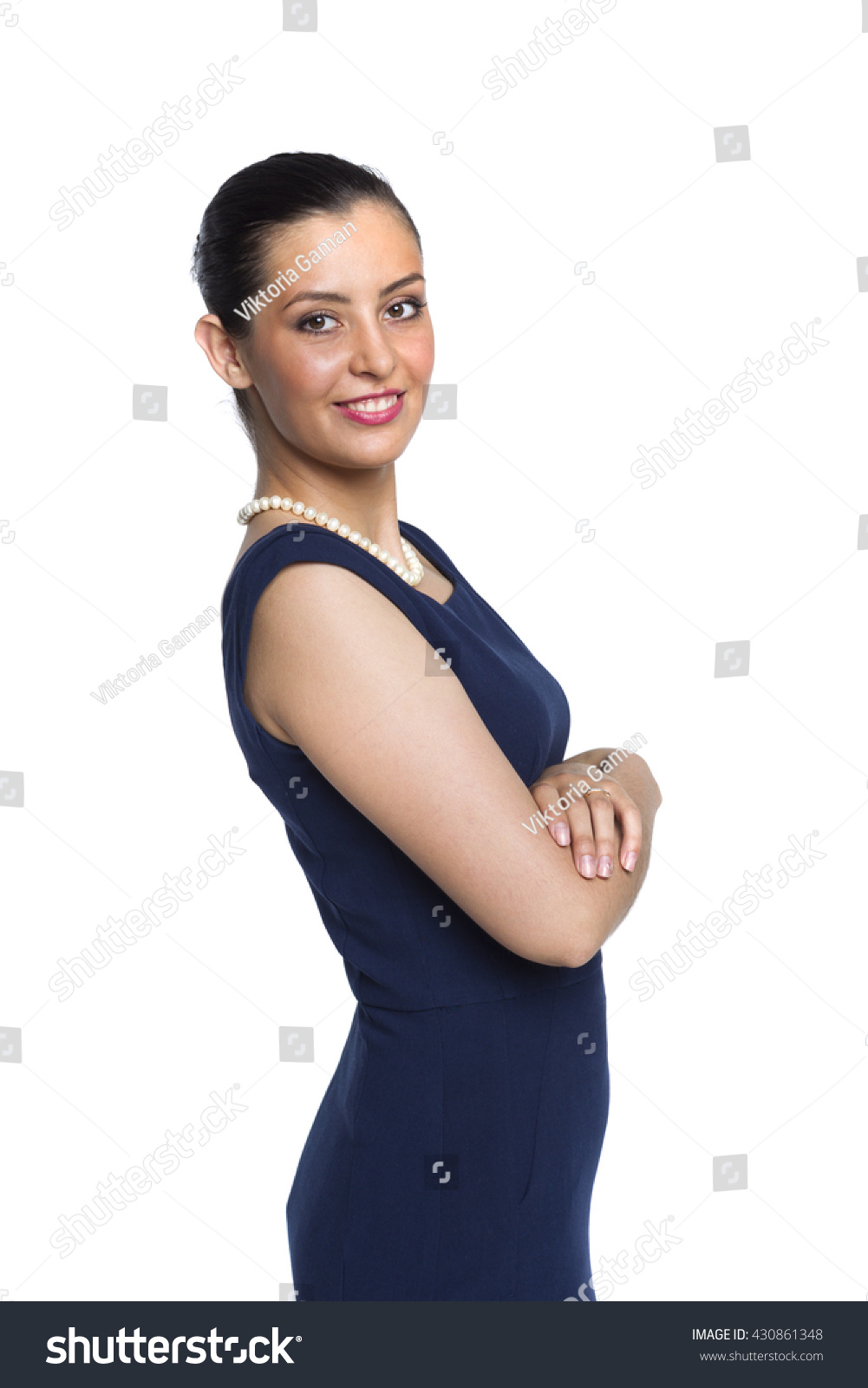 Young Woman In Strict Blue Dress With A Pearl Necklace, In A Closed  Position,