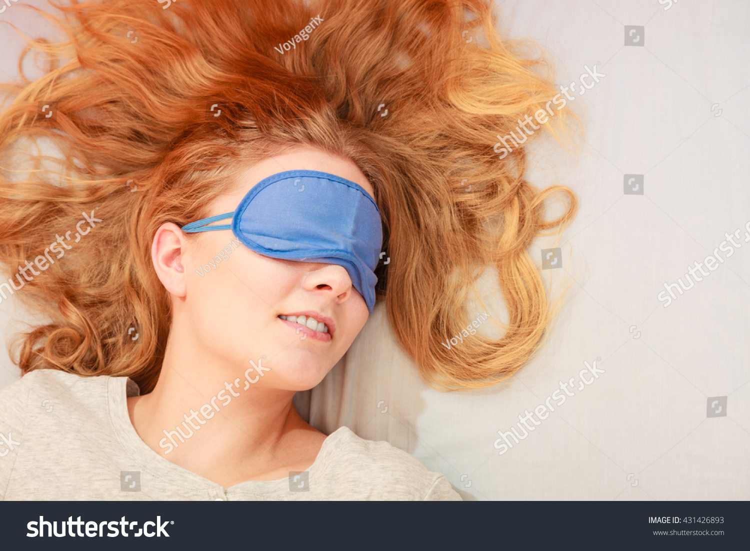 5f2166c84e5 Tired woman sleeping in bed wearing blindfold sleep mask. Young girl taking  nap.