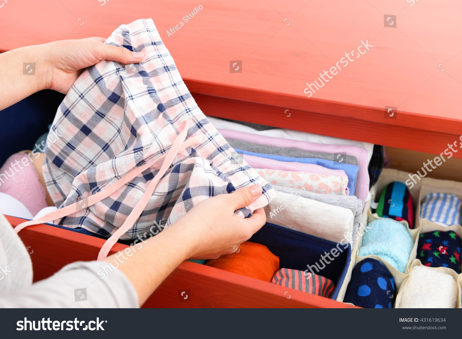 Woman folding clothes into chest of drawers closeup #431619634