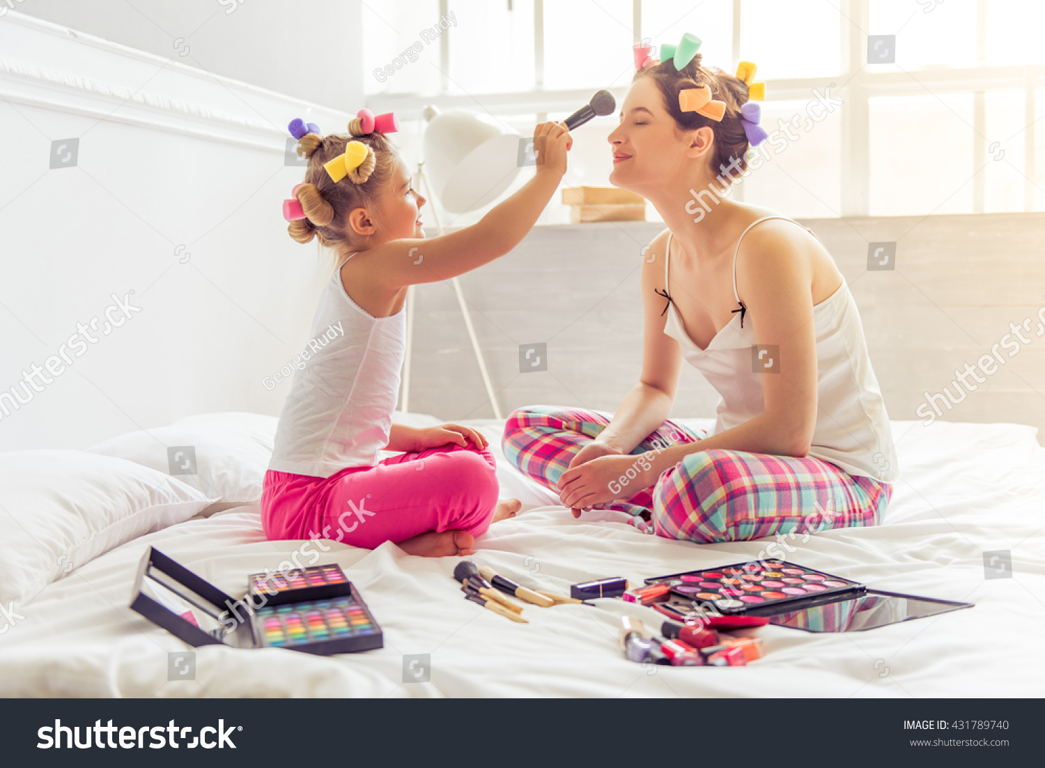 Beautiful young mother and her daughter in pajamas and with hair curlers on bed at home Cute little girl is doing her mother makeup