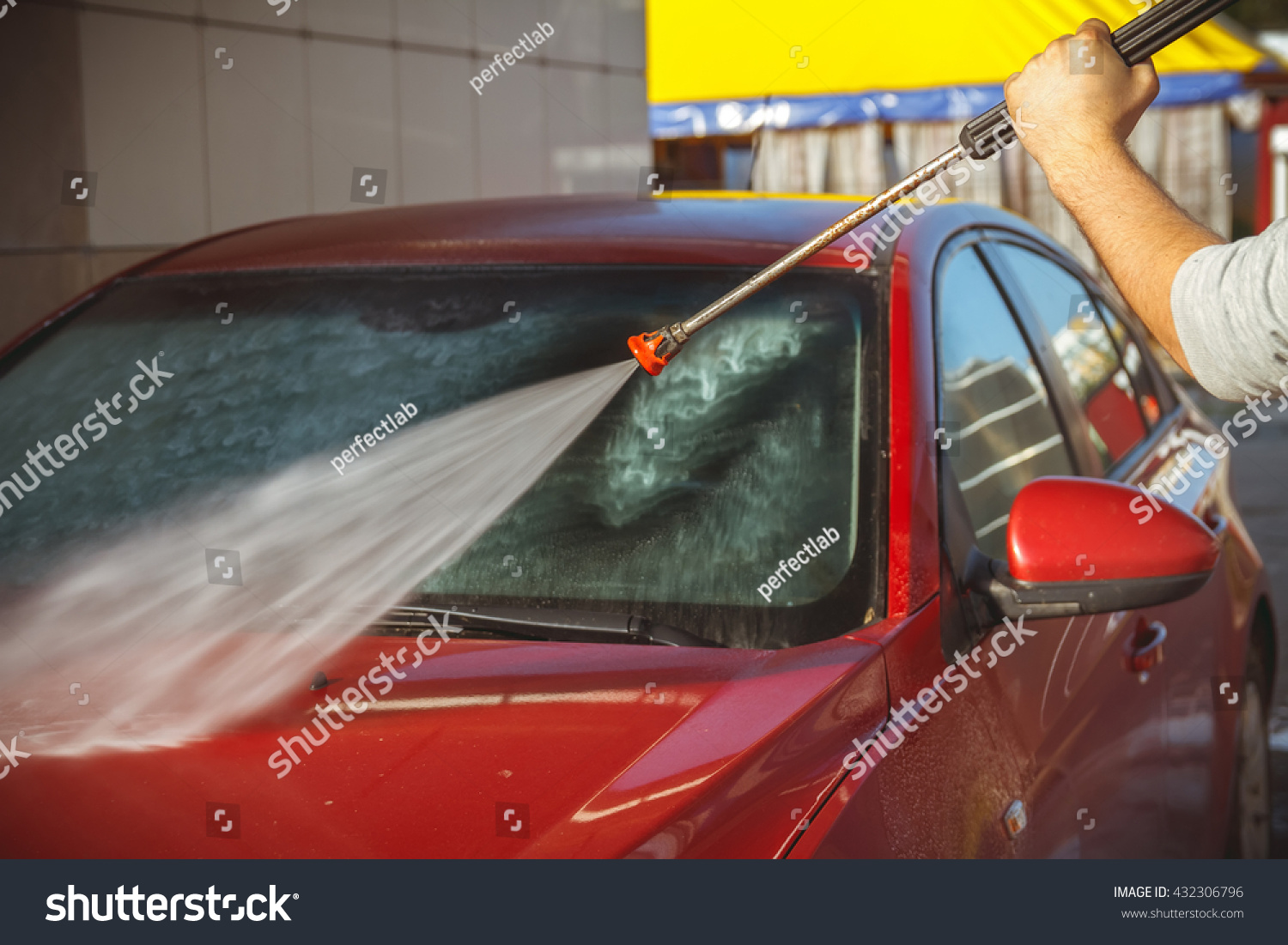 Contactless car wash self-service. Young man washing his car #432306796