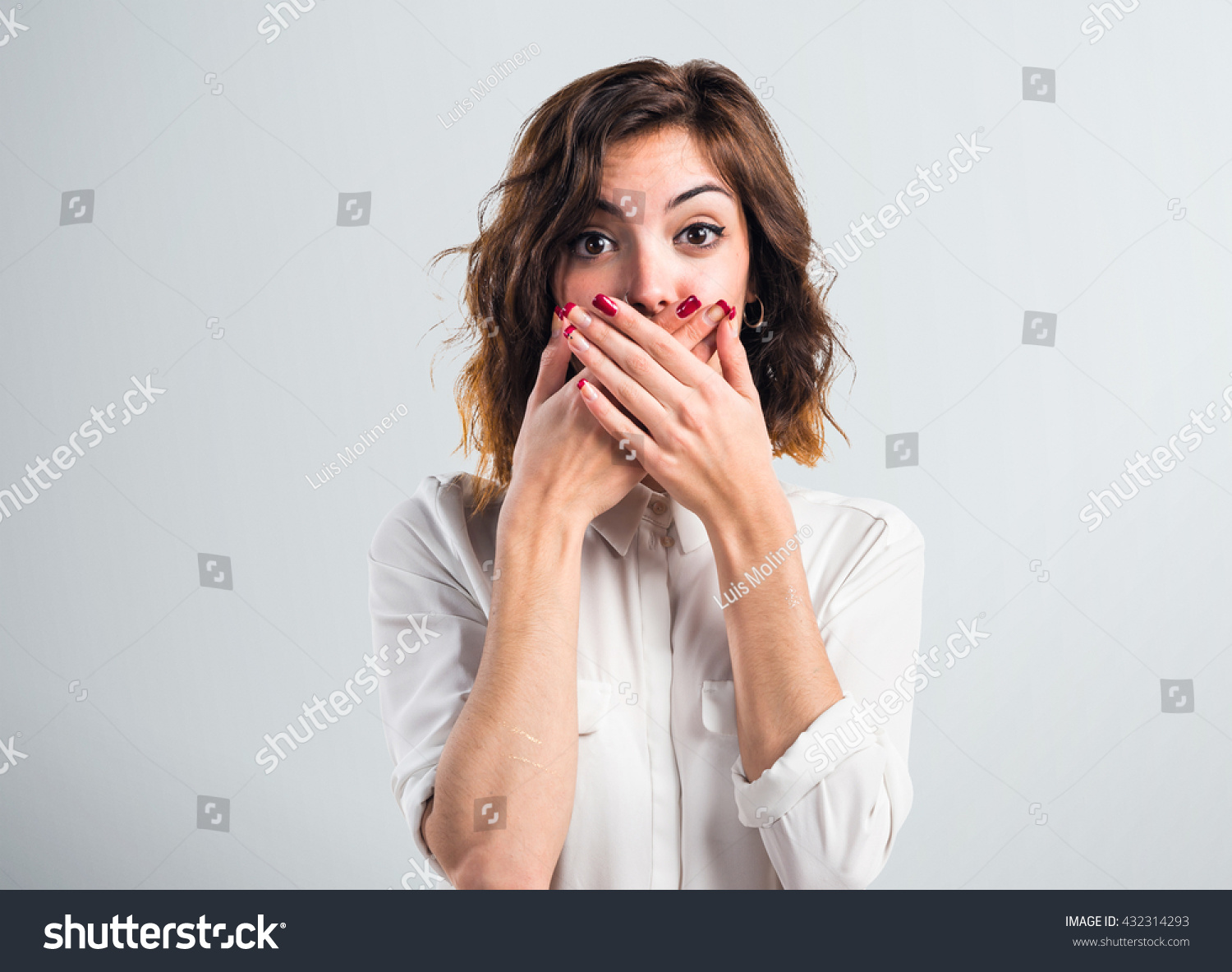Pretty girl covering her mouth over grey background #432314293