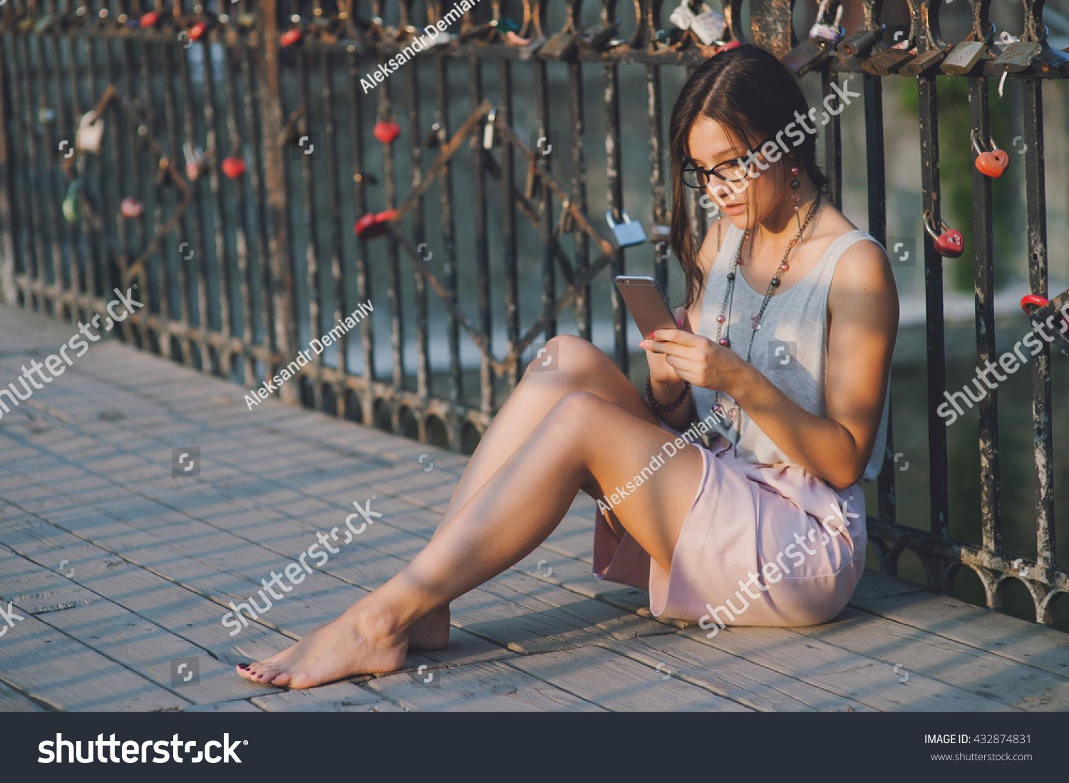 https://image.shutterstock.com/z/stock-photo-beautiful-girl-send-a-massage-with-a-smart-phone-sitting-on-a-bridge-evening-sunset-432874831.jpg