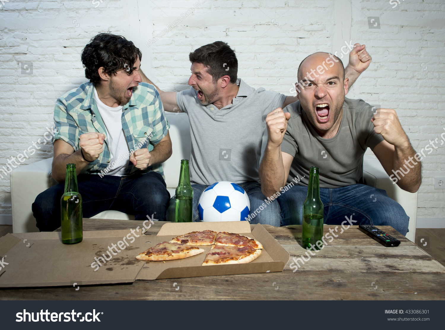 Fans taking pictures with cell phone behind barrier stock photo - Group Of Friends Fanatic Football Fans Watching Soccer Game On Television Celebrating Goal On Couch Screaming