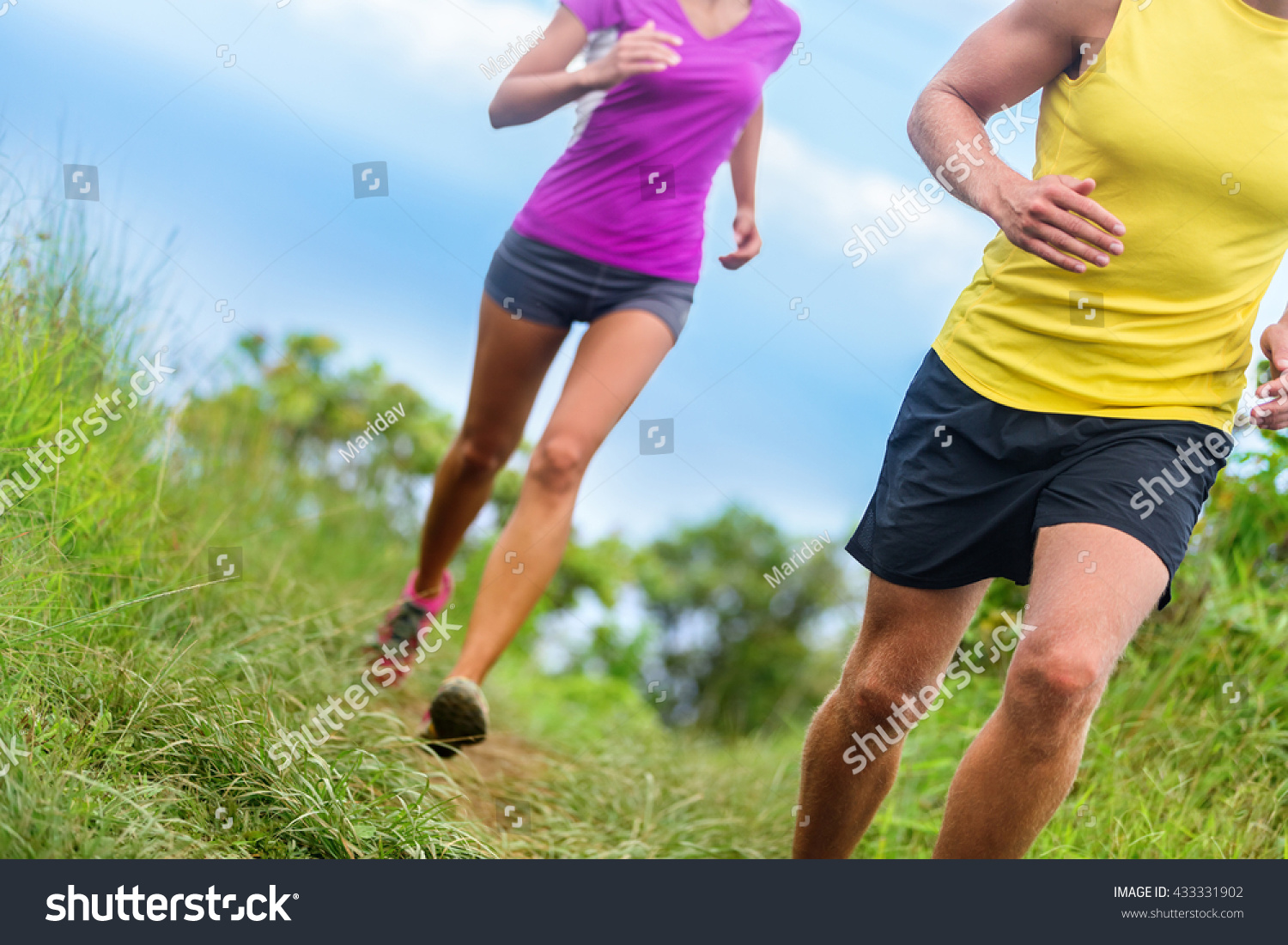 Fitness athletes trail running athletic legs closeup lower body crop of man and woman working out Sports people jogging in fast motion marathon race training on a nature path in shorts activewear