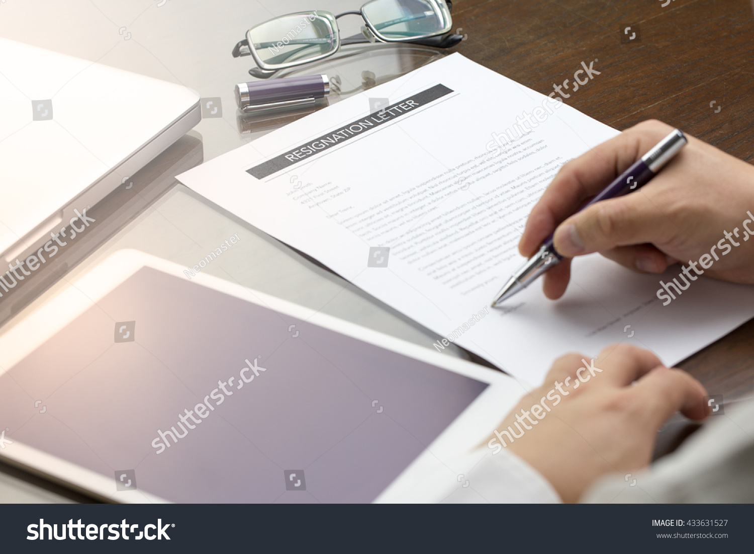 Business man signing his resignation letter on
