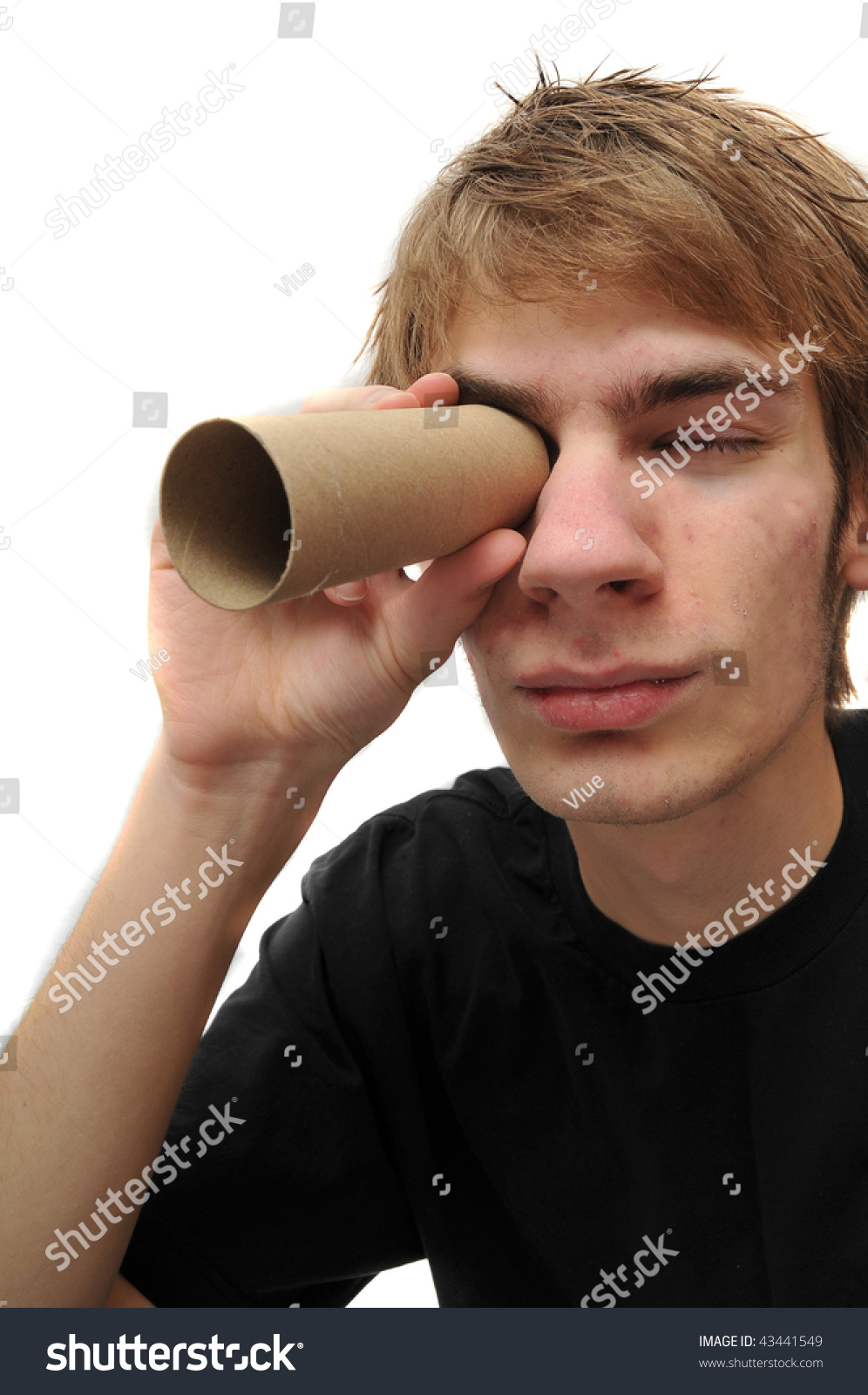 Young adult looking through brown cardboard toilet paper roll tube isolated  on white