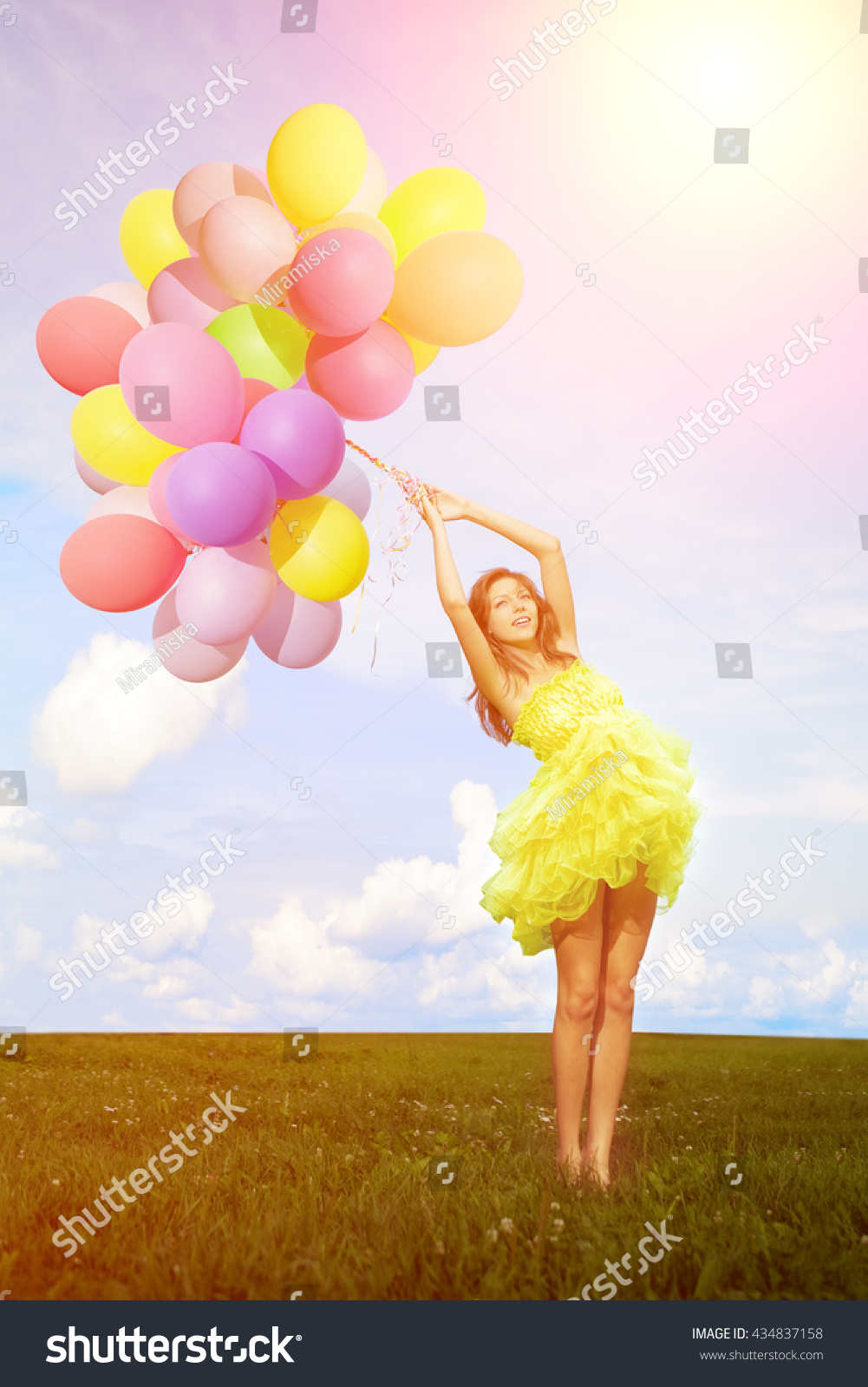 happy birthday woman against the sky with rainbow colored air balloons in hands sunny and positive energy of nature young beautiful girl on the grass in