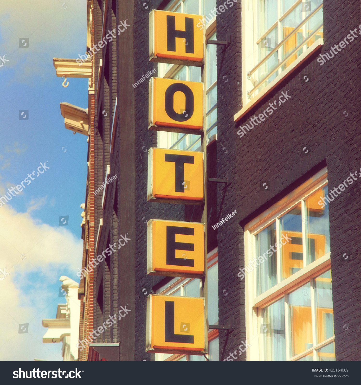 Vertical Yellow Hotel Sign Over The Entrance To Brick Building In Amsterdam Vintage Toned
