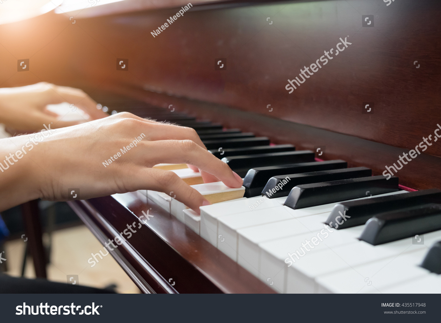 Close up of young girls hands playing piano