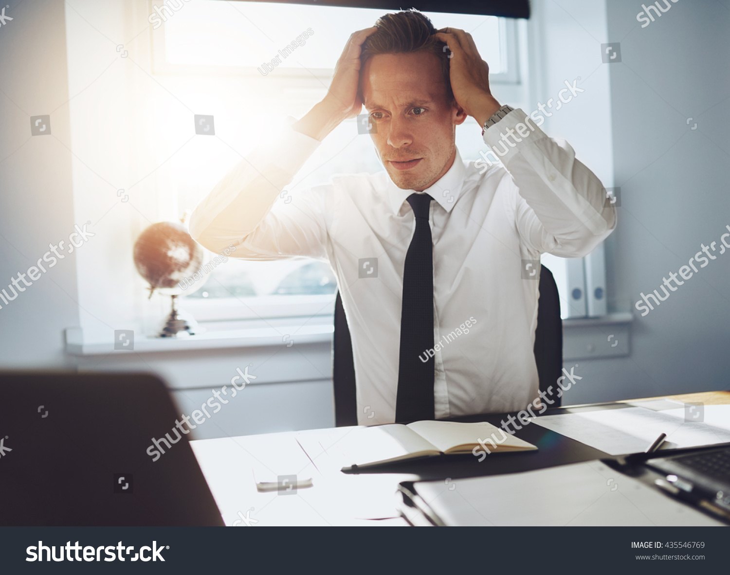 Frustrated office worker on the phone holding stock photo image - Frustrated Business Man Looking At Laptop Holding His Hands To His Head In Frustration