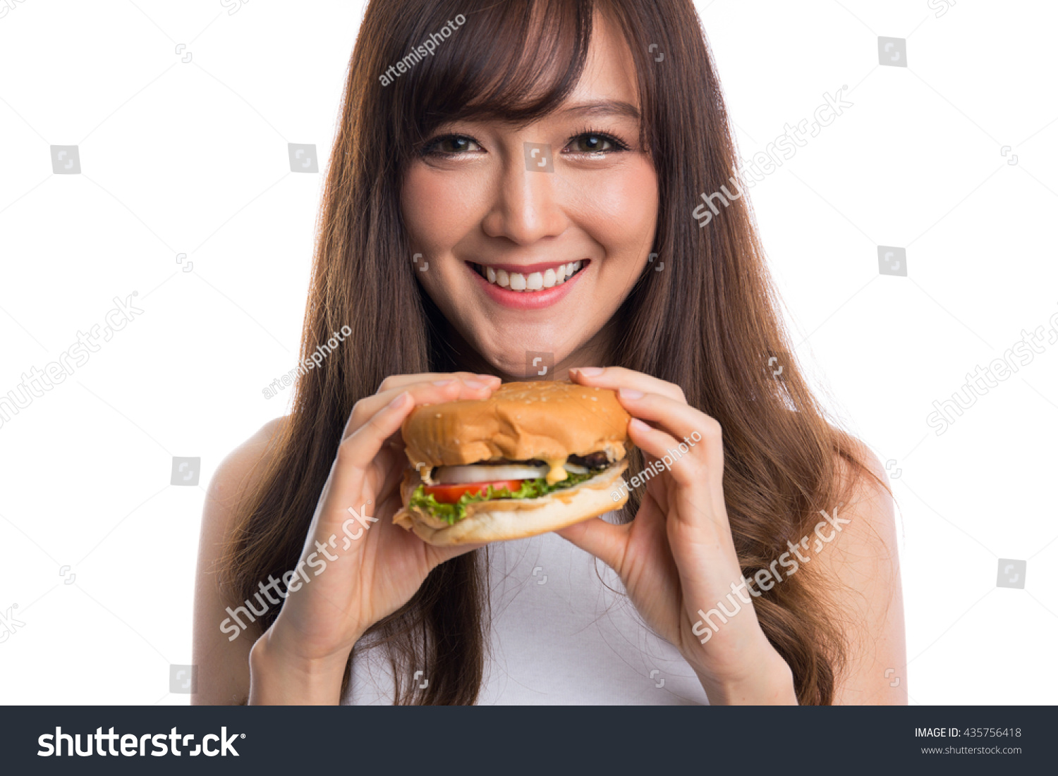 Young asian woman eating burger on white background, unhealthy eating and  diet concepts.