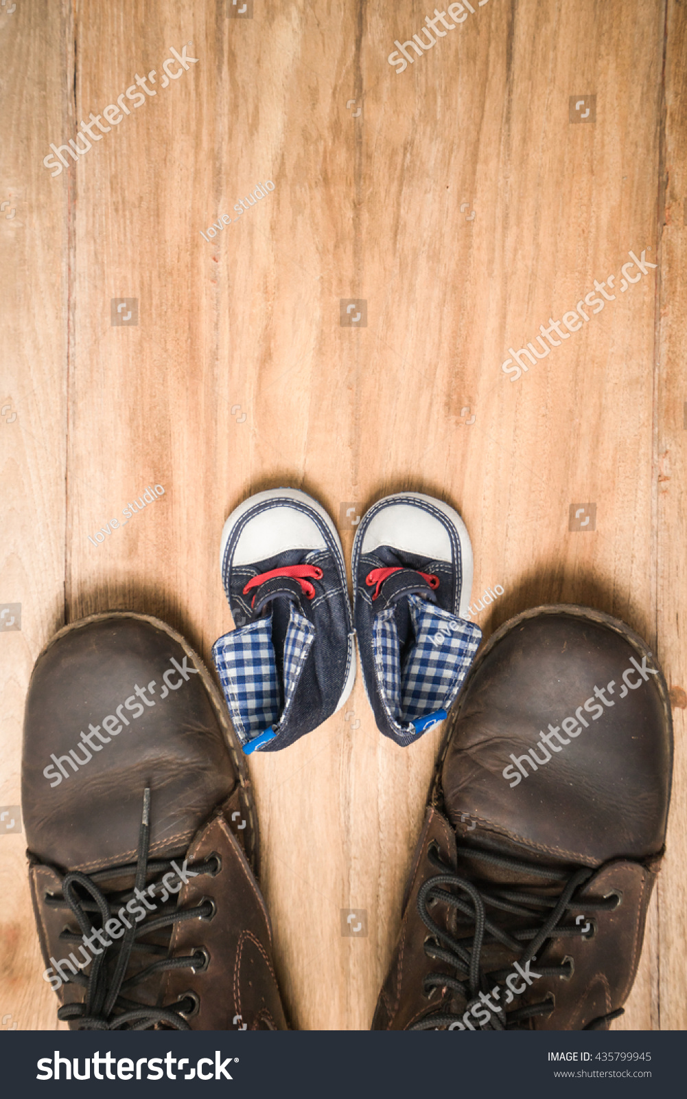 Daddy's boots and baby's sneakers on wood background fathers day concept.flat lay