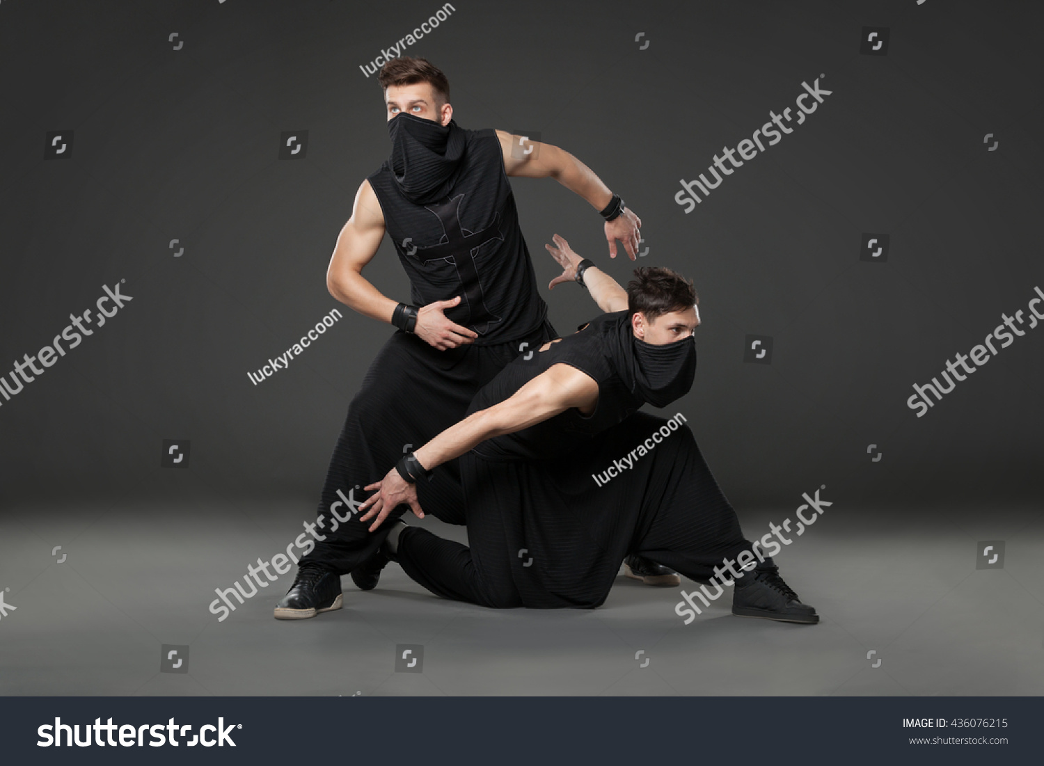 993ff8a1425d9 Two male dancers dancing in ninja costumes against gray background.