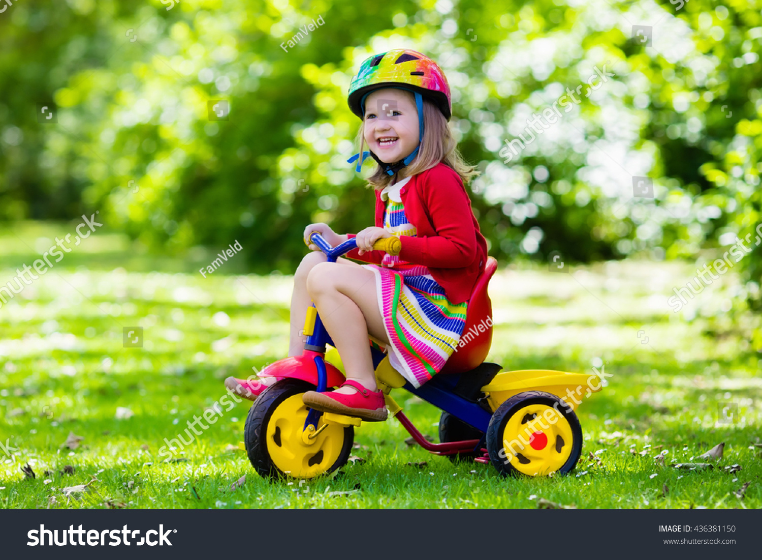 94ca829ac61 Cute girl wearing safety helmet riding her tricycle in sunny summer park.  Kids ride bicycle