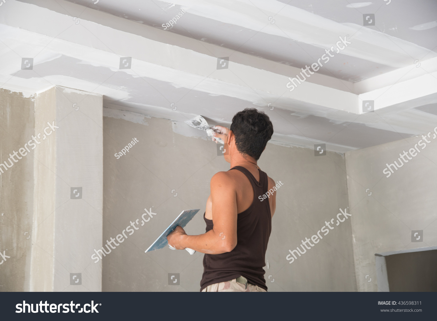 Worker Working Manual With Wall Plastering Tools Inside A House. Plasterer  Renovating Indoor Walls And