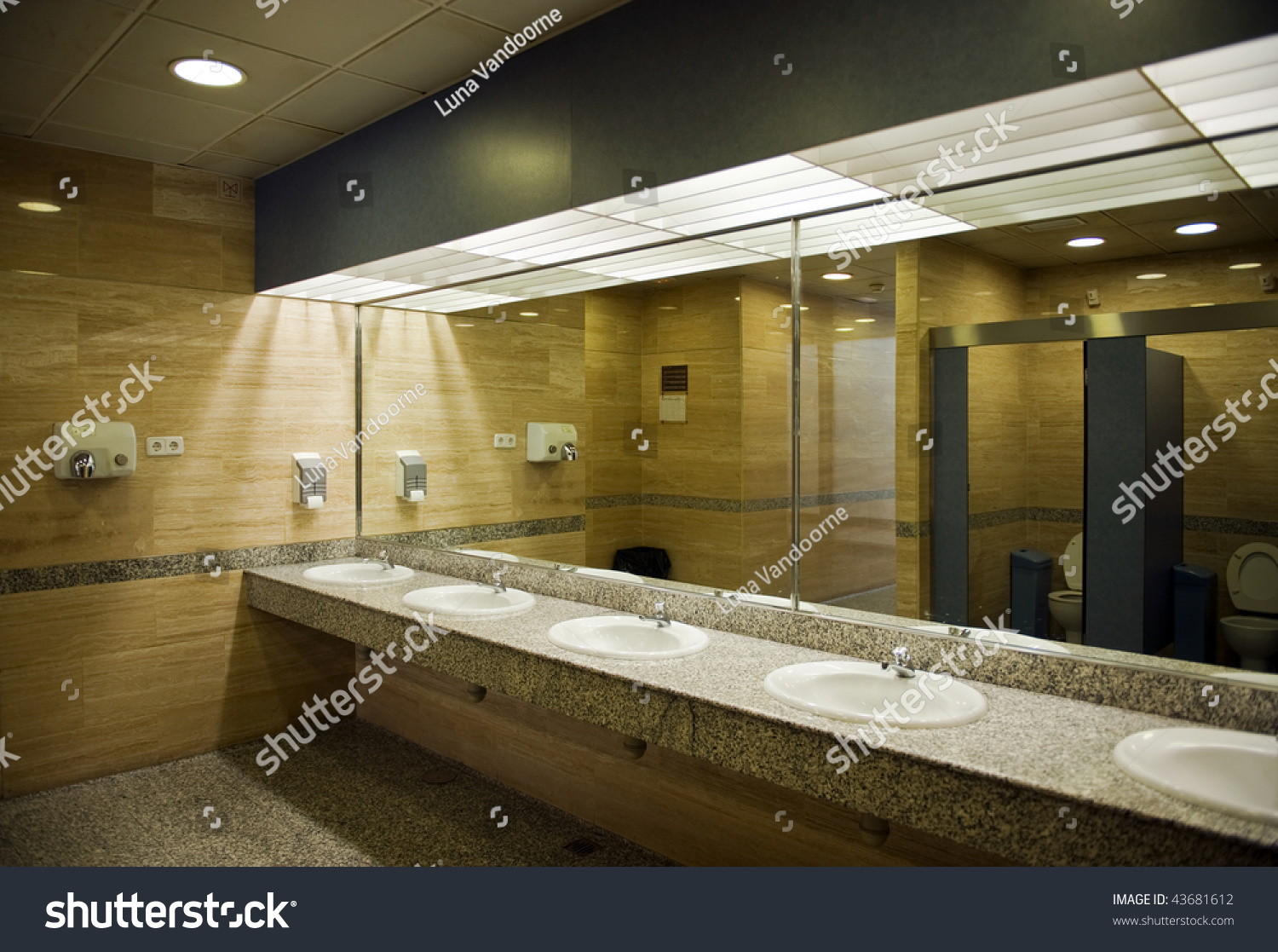 Public Empty Restroom With Washstands And Toilets In Mirror Stock