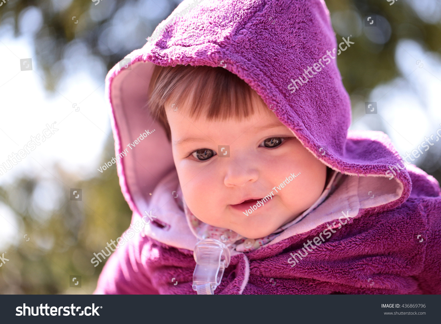 small cute baby girl with pretty face and funny eyes in hood sunny
