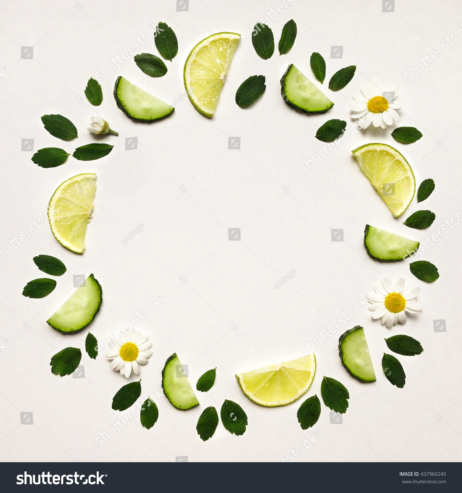 Colorful frame with fresh citrus fruits cucumbers leaves and flowers Flat lay on white table