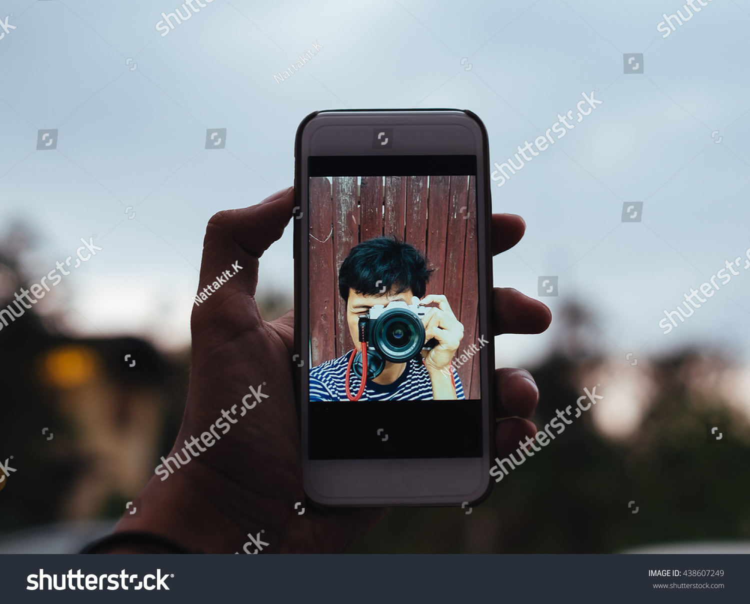one young adult asian man shooting himself, take a selfie alone with smart  phone and