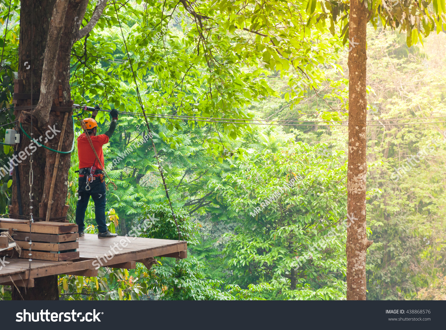adventure zipline high wire park - people on course in mountain helmet and safety equipment,ready to descend on zipline in forest, extreme sport #438868576