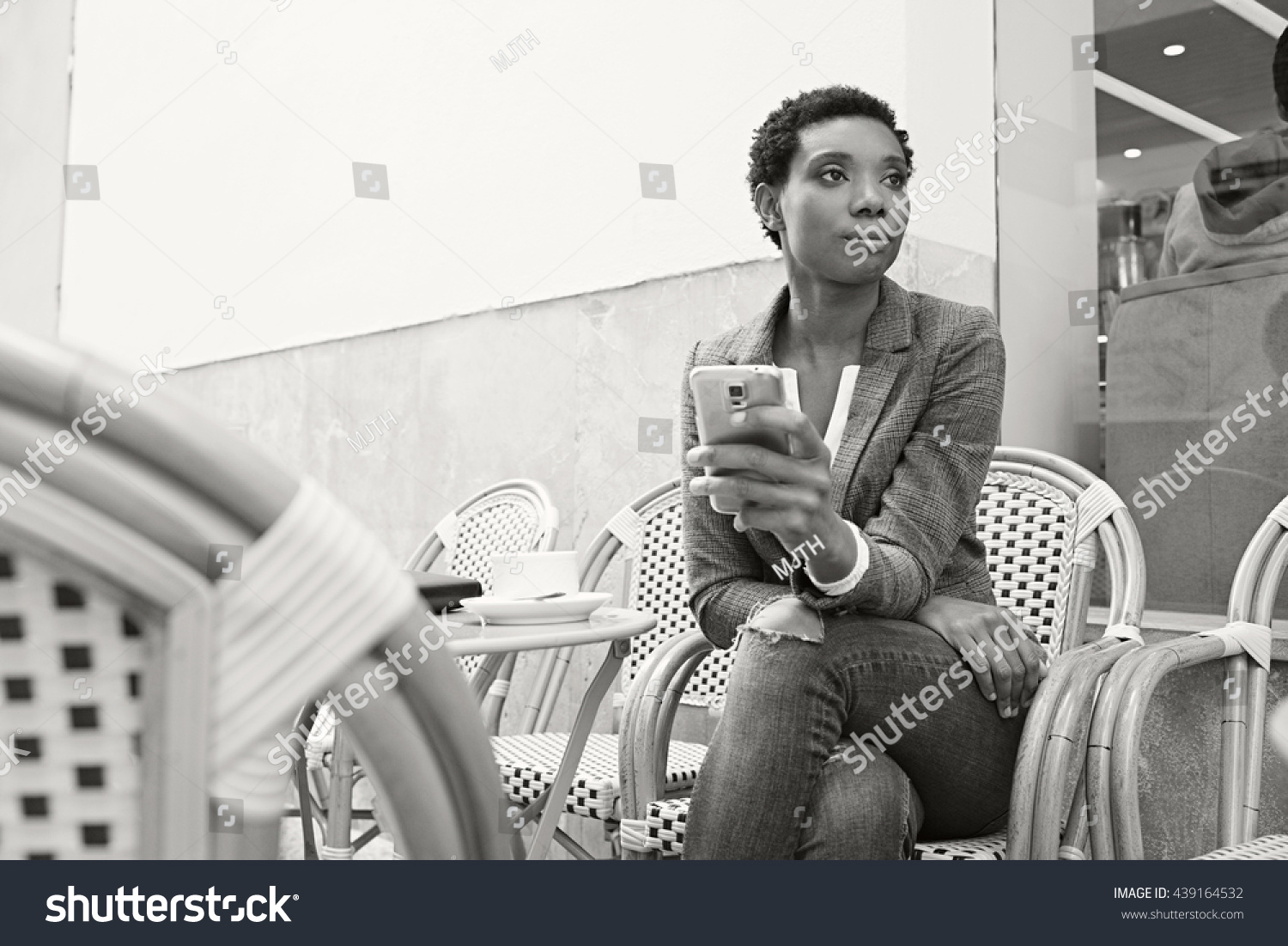 Black and white portrait of beautiful african american business woman in coffee shop terrace drinking coffee
