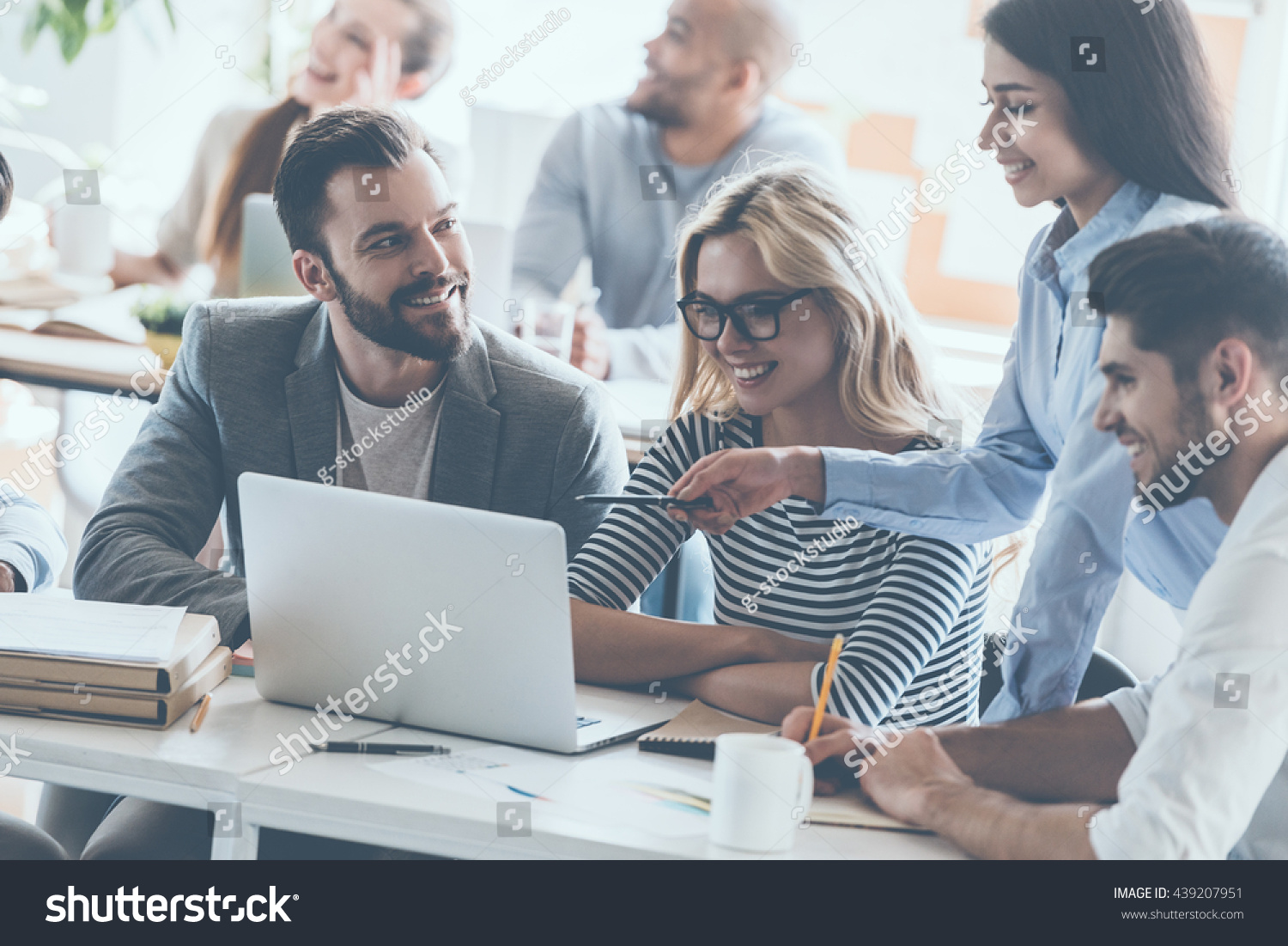We got great results! Group of young cheerful business people working and communicating while sitting at the office desk together with colleagues sitting in the background  #439207951